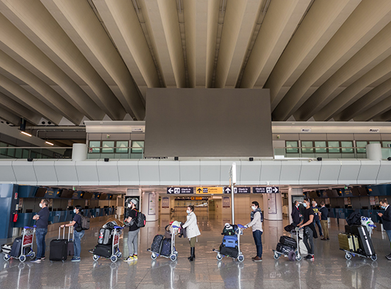 Rome, Italy - june 3, 2020: First passengers after Covid 19 pandemic lockdown in Rome Fiumicino Airport. Line of people waiting for boarding in airport keeping one meter social distance.